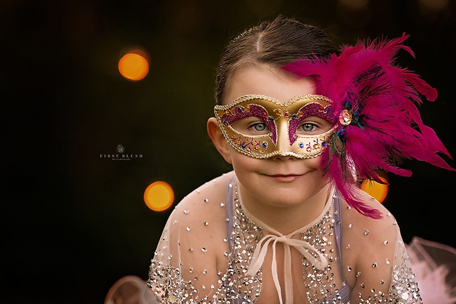 Child wearing Mardi Gras mask with pink feathers smiles at the camera using Make them smile Philosophy.