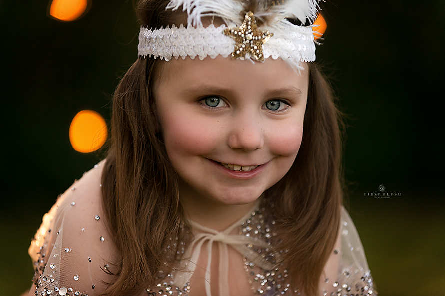 Little girl smiles at the camera using First Blush philosophy near Red Deer Alberta